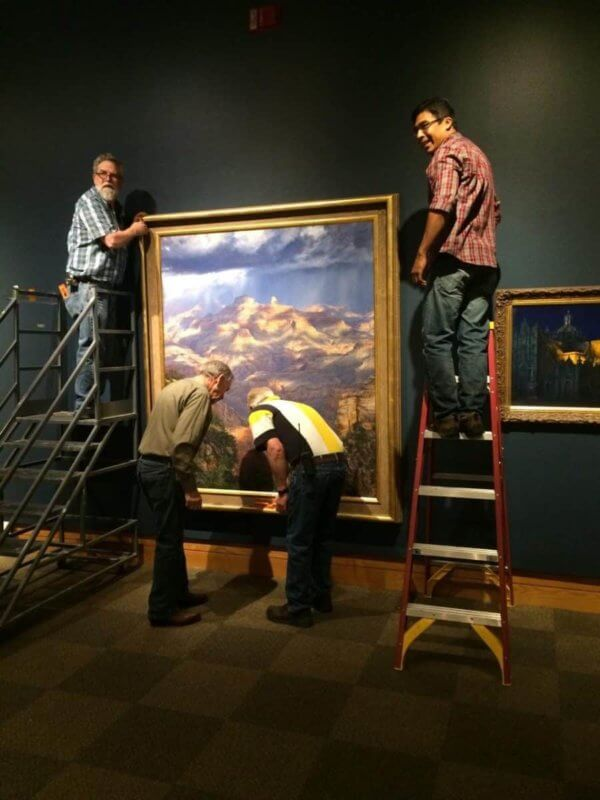 a group of people assisting in the Hanging of a large Curt Walters painting at Prix de West